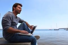 Mężczyzna siedzący jeziorem Zdjęcie Royalty Free
