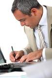 Mężczyzna siedzący przy jego biurka writing Fotografia Stock