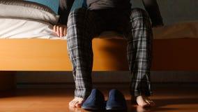 Mężczyzna siedzi na łóżku w nocy w domu Obrazy Royalty Free