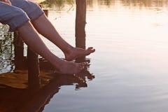 Mężczyzna siedzi na drewnianym moscie i upadów ciekach w ciepłej wodzie dla jeziora w lecie Obrazy Royalty Free