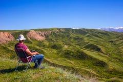 Mężczyzna siedzi na krześle i egzamininuje otaczającego krajobraz obrazy royalty free