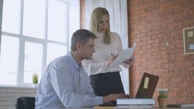 Mężczyzna siedzi na krześle w biurze i młoda kobieta stoi blisko, oba jest przyglądająca na papierze na stole, dyrektor zbiory
