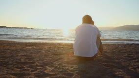 Mężczyzna siedzi na plaży zbiory wideo