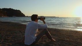 Mężczyzna siedzi na plaży zdjęcie wideo