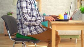 Mężczyzna siedzi na round ortopedycznej poduszce i zaczyna pracować na laptopie zamkniętym w górę zdjęcie wideo