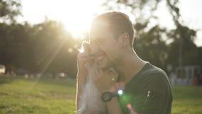 Mężczyzna siedzi na trawie w zielonym parku, sztuka z młodym małym psem Właściciel dokucza doggy, bawić się i ściska, Ono uśmiech zdjęcie wideo