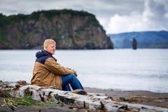 Mężczyzna siedzi na wybrzeżu Avacha zatoka przy Kamchatka obrazy stock