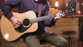 Mężczyzna siedzi na wysokiego baru krześle i bawić się gitarę akustyczną zbiory wideo