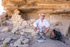 Mężczyzna siedzi odpoczynkowych moutains falezy rockowego schronienie zdjęcie stock