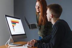 Mężczyzna siedzi przed komputerem i mówi kobiecie coś Pokazuje liczbę sprzedaże fotografia stock