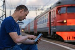 Mężczyzna siedzi przy dworcem elektryczni pociągi i co jest przyglądający dla smartphone wewnątrz zdjęcia royalty free