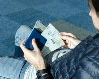 Mężczyzna siedzi przy lotniskiem i trzyma w w cajgach ręka samolotowych biletach paszporcie i zdjęcie stock