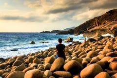 Mężczyzna Siedzi Samotnie z Jego Thoughs przy Dziką Eggshaped skały plażą z Dramatycznymi chmurami w niebie zdjęcia royalty free