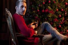 Mężczyzna siedzi w krześle i trzymać telefon Fotografia Royalty Free