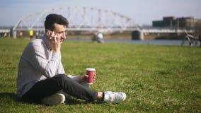 Mężczyzna siedzi w parku na trawie, opowiada na telefonie Uczeń komunikuje na telefonie, śmiechy, uśmiechy _ zbiory