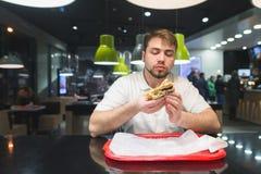 Mężczyzna siedzi w restauraci i je fast food Mężczyzna je apetycznego hamburger Fasta food pojęcie Zdjęcia Royalty Free