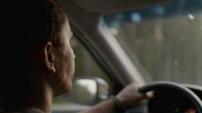 Mężczyzna siedzi w samochodzie i patrzeje naprzód droga zdjęcie wideo