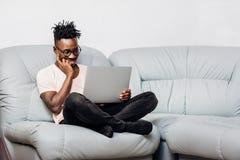Mężczyzna siedzi z laptopem na kanapie w szkłach fotografia stock