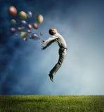 Mężczyzna skacze do niebo dowcipu koloru jaskrawego balonu Obrazy Royalty Free