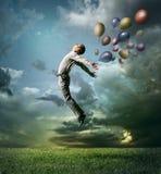 Mężczyzna skacze do niebo dowcipu koloru jaskrawego balonu Obraz Stock
