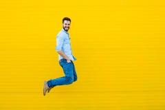 Mężczyzna skacze na żółtym tle fotografia royalty free