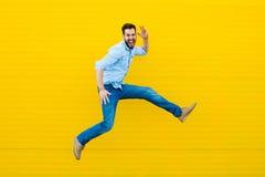 Mężczyzna skacze na żółtym tle zdjęcia stock