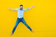 Mężczyzna skacze na żółtym tle obrazy stock