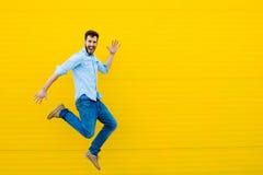 Mężczyzna skacze na żółtym tle zdjęcie royalty free