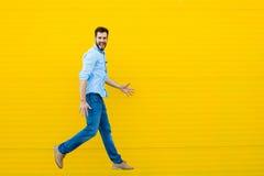 Mężczyzna skacze na żółtym tle obraz royalty free