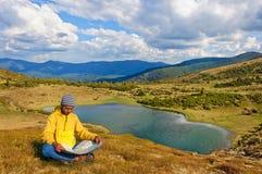 Mężczyzna skupia się na mapie blisko jeziora w Karpackich górach Ukraina fotografia stock
