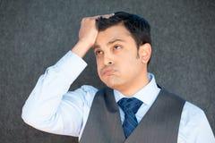 Mężczyzna spęczenie z ręką na głowie zdjęcia royalty free