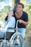 Mężczyzna spaceruje z niepełnosprawną kobietą w drewnach obrazy royalty free