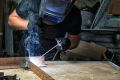 Mężczyzna spawa metalu łuku spawalniczą maszynę zdjęcie stock