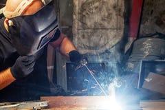 Mężczyzna spawa metalu łuku spawalniczą maszynę fotografia stock