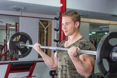Mężczyzna spełniania barbell kędzior przy gym fotografia royalty free