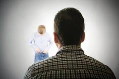 Mężczyzna spojrzenia przy chłopiec fotografia stock