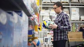 Mężczyzna spojrzenia przy siatkówki i piłki nożnej piłkami w hypermarket dla sporty gemowi zbiory wideo