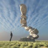 Mężczyzna spojrzenia przy skałami umieszczać w równowadze Obrazy Stock