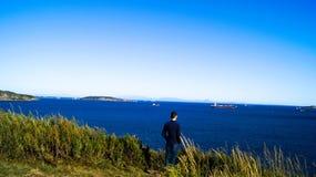Mężczyzna spojrzenia przy statkami na plaży Obrazy Stock