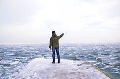 Mężczyzna spojrzenia przy zamarzniętym morzem Fotografia Royalty Free