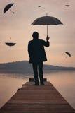 Mężczyzna spojrzenia przy zmierzchu niebem pełno parasole Fotografia Stock