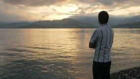 Mężczyzna spojrzenia w koszula patrzeje wschód słońca na plaży ocean Słońce wzrasta od gór za _ zbiory