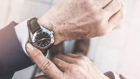 Mężczyzna sprawdza czas jego zegarek zdjęcie stock