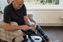 Mężczyzna Sprawdza glikoza poziomy w domu fotografia stock