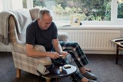 Mężczyzna Sprawdza glikoza poziomy w domu fotografia royalty free