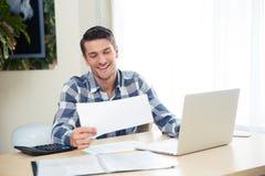 Mężczyzna sprawdza rachunki na pastylce w domu Obraz Royalty Free