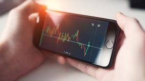 mężczyzna sprawdza rynek papierów wartościowych na smartphone zdjęcie wideo