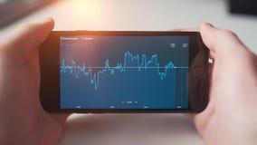 mężczyzna sprawdza rynek papierów wartościowych na smartphone zbiory