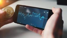 Mężczyzna sprawdza rynek papierów wartościowych na smartphone z btc bitcoin zbiory wideo