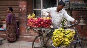 Mężczyzna sprzedaje banany i jabłka na rowerze Fotografia Stock